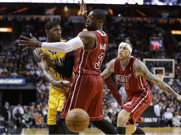 Indiana Pacers' Paul George (24) passes the ball as Miami Heat's Dwyane Wade (3) defends in the first half of an NBA basketball game, Wednesday, Dec. 18, 2013, in Miami. At right is Chris Ande