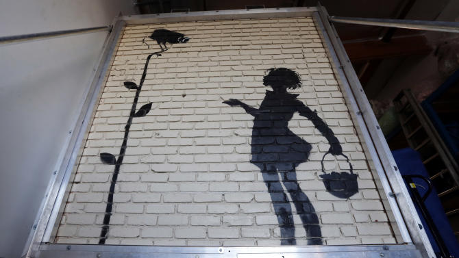 """FILE - This Dec. 4, 2013 file photo shows """"Flower Girl,"""" a stencil on a massive brick wall by popular street artist Banksy, is displayed in a warehouse in Los Angeles. The mural stenciled on the side of a Hollywood gas station five years ago has fetched more than $200,000 at a Beverly Hills auction on Thursday Dec. 5, 2013. (AP Photo/Reed Saxon,File)"""