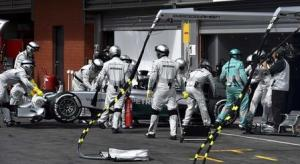 Mechanics push the car of Mercedes driver Hamilton in the pit after he retired from the Belgian F1 Grand Prix in Spa-Francorchamps