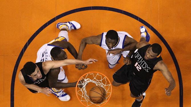 Devin Booker (L) of the Phoenix Suns attempts a lay up over Draymond Green of the Golden State Warriors as T.J. Warren (R) looks for a rebound at Talking Stick Resort Arena on November 27, 2015 in Phoenix, Arizona