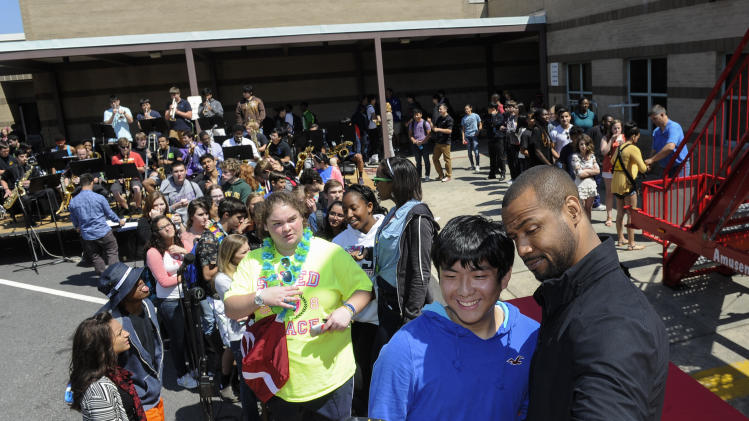 "As part of the national Old Spice Scent Responsibly school tour, the world-famous ""Old Spice Guy"" Isaiah Mustafa, right, takes selfies with students at Chattahoochee High School's annual Springfest on Thursday, April 17, 2014 in Johns Creek, Ga. (Photo by John Amis/Invision for Old Spice/AP Images)"