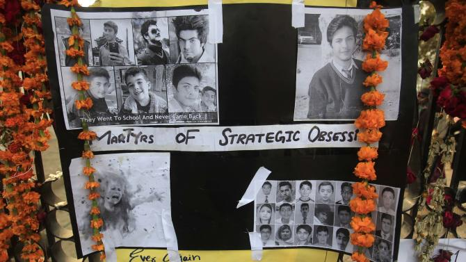 Pictures of victims of Tuesday's attack on Army Public School are displayed at the gate of the school in Peshawar