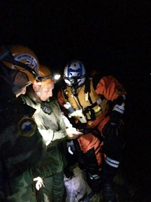 In this photo provided by the Los Angeles Sheriff's Department, Malibu Search and Rescue Team members assist four stranded hikers who were trapped overnight March 1, 2014 in a remote area of Malibu Creek State Park, Calif. Although the initial rescue area was inaccessible, the helicopter was finally able to connect with rescuers shortly after 3 a.m. and airlift the hikers to safety.(AP Photo/Los Angeles Sheriff's Department)