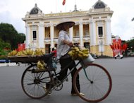 A hawker is seen pushing her bicycle past the Opera House in Hanoi. Vietnam&#39;s inflation accelerated for the first time in 12 months in September, up 6.48 percent on a year earlier, amid fears of a return to rocketing prices as the country grapples with multiple economic woes