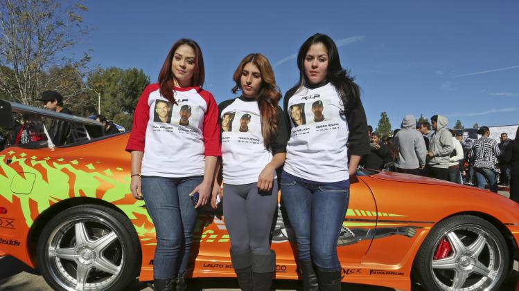 "Women wear shirts commemorating ""Fast & Furious"" star Walker and Rodas during an unofficial memorial event in Santa Clarita"