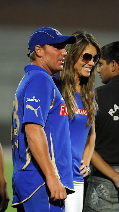 RESTRICTED TO EDITORIAL USE. MOBILE USE WITHIN NEWS PACKAGE Rajasthan Royals captain Shane Warne talks his girlfriend Liz Hurley (R) after victory during the IPL Twenty20 match between Kochi Tuskers K