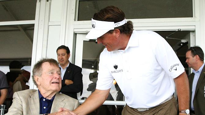 Phil Mickelson visits with former president George H.W. Bush after completing the third round of the Houston Open golf tournament, Saturday, March, 30, 2013, in Humble, Texas. (AP Photo/Patric Schneider)