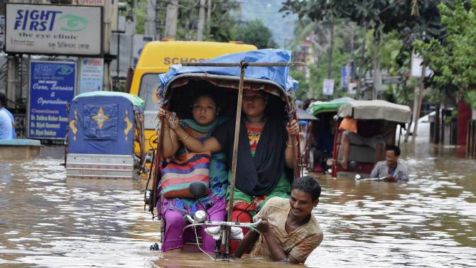 People use cycle rickshaws to commute through a flooded road after heavy rains in Guwahati