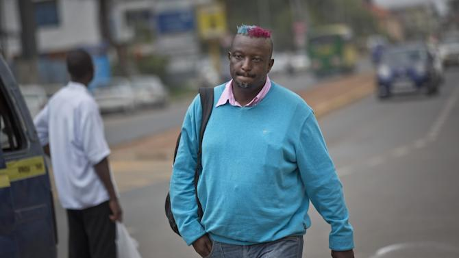 Prize-winning Kenyan author Binyavanga Wainaina walks down a street in Nairobi, Kenya Wednesday, Jan. 22, 2014. Wainaina, one of Africa's leading literary figures, spoke to The Associated Press on Wednesday to explain his decision to publicly declare his homosexuality in an online essay last weekend, in light of a wave of new legislation further criminalizing homosexuality in Nigeria and Uganda. (AP Photo/Ben Curtis)
