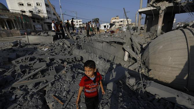 A Palestinian boy walks through the rubble of a mosque targeted in an Israeli airstrike in Gaza City on August 25, 2014