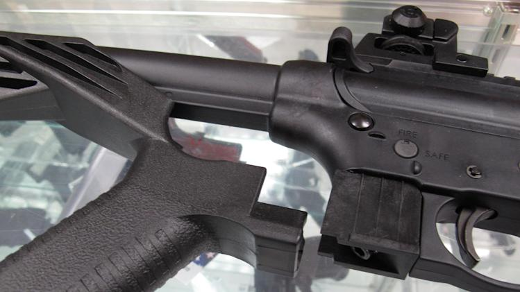 "This Feb. 1, 2013 photo shows a ""bump"" stock next to a disassembled .22-caliber rifle at North Raleigh Guns in Raleigh, N.C. The accessory devices, which legally allow a semiautomatic rifle to fire like a real machine gun, are among nearly 160 weapons or accessories targeted by a proposed federal ban. (AP Photo/Allen Breed)"