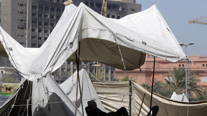 An Egyptian protester takes a nap under his tent in Tahrir Square, which has been closed to vehicle traffic for months, in Cairo, Egypt, Monday, March 11, 2013. Egypt's ruling Muslim Brotherhood called on revolution forces to condemn acts of vandalism and temporarily suspend demonstrations, media spokesperson Ahmed Aref said. (AP Photo/Amr Nabil)