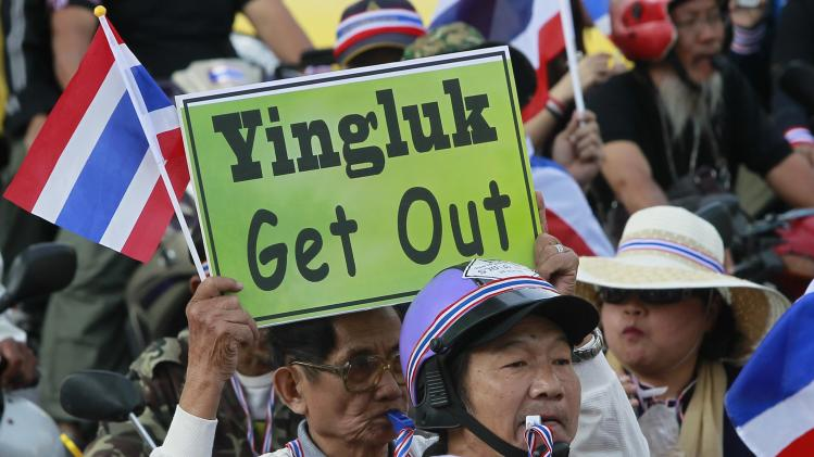 An anti-government protester blows whistle and holds placard in rally at major business district in Bangkok