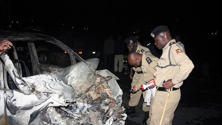 In this photo taken on late Saturday night June 30, 2013, Ugandan police inspect a mangled car in Uganda capital Kampala. A car crashed into a moving gas tanker, sparking a fire that killed at least 29 people and left scores more badly burned, Ugandan police said on Sunday. Police spokesman Ibn Senkumbi said the gas tanker exploded after colliding with a passenger car late Saturday on the outskirts of the Ugandan capital, Kampala.(AP Photo)