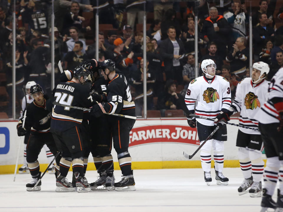 Anaheim Ducks' Peter Holland (74) is congratulated by Bryan Allen (55) and Luca Sbisa (5), of Italy, after scoring a goal against the Chicago Blackhawks during the first period of an NHL hockey game in Anaheim, Calif., Wednesday, March 20, 2013. (AP Photo/Jae C. Hong)