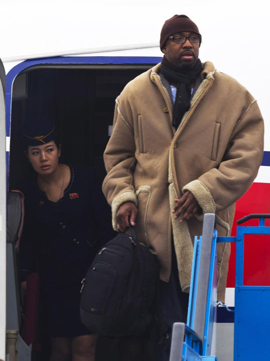 A North Korean Air Koryo flight attendant peeks out from the aircraft door as former NBA basketball player Vin Baker arrives at the international airport in Pyongyang, North Korea Monday, Jan. 6, 2014