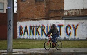 A man rides his bike past graffiti in Detroit