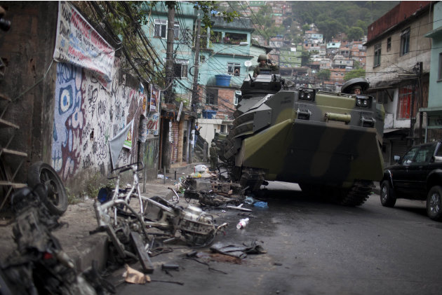A Brazilian navy armored vehicle runs over motorcycles as it moves into Rocinha shantytown in Rio de Janeiro, Brazil, Sunday Nov.  13, 2011. Brazilian police backed by armored military vehicles have i