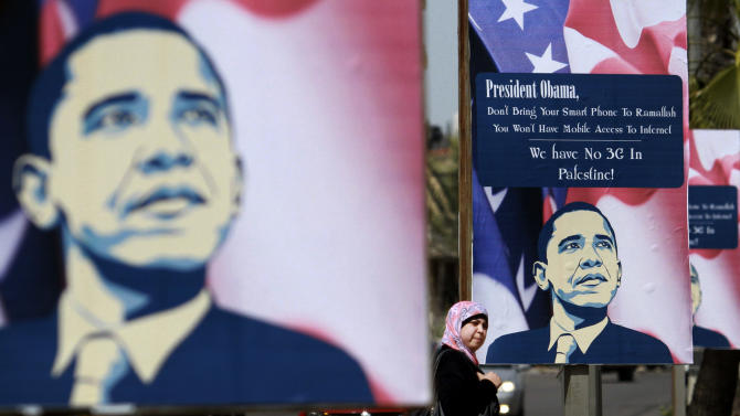 In this Tuesday , March 12, 2013 photo, a Palestinian woman walks past posters showing US President Barack Obama in the West Bank city of Ramallah. Obama's trip to Jerusalem and the West Bank, which Israeli officials say will take place March 20-22, is the U.S. leader's first trip to the region as president, and his first overseas trip since being reelected. (AP Photo/Nasser Shiyoukhi)