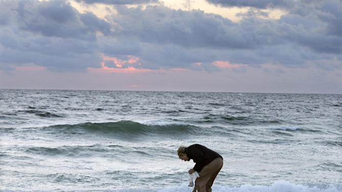 As the sunrises, Sue Dougherty looks for shells along the beach In Seaside Heights, N.J., Tuesday, Oct. 29, 2013. Tuesday marks the one-year anniversary of Superstorm Sandy. (AP Photo/Mel Evans)