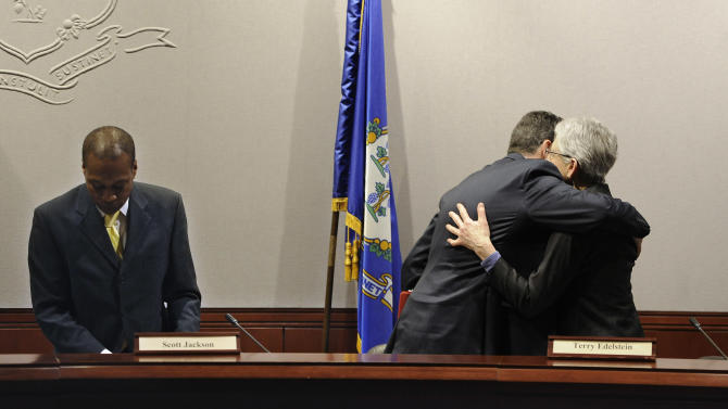 Connecticut Gov. Dannel P. Malloy embraces commission member Terry Edelstein, right, as Commission Chair and Mayor of Hamden Scott Jackson prepares to leave at the conclusion of a presentation of the final report from the Sandy Hook Advisory Commission at the Legislative Office Building, Friday, March 6, 2015, in Hartford, Conn.  The commission was formed to provide a review current policy and make recommendations in the areas of public safety, mental health, and gun violence prevention after the 2012 killings of 20 first-graders and six adults at Sandy Hook Elementary School. (AP Photo/Jessica Hill)