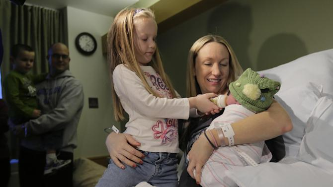 Noelle Joy Klinker, of Reading, Mass., who was born at 12:12pm at the Massachusetts General Hospital, rests in her mother Colleen's arms as her sister Gracie, 5, feeds her a few hours after birth on Wednesday, Dec. 12, 2012 in Boston. Noelle was a natural birth. (AP Photo/Charles Krupa)