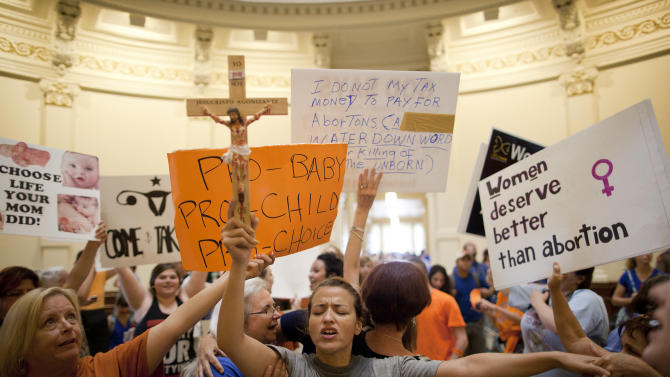 Anti-abortion rights supporter Katherine Aguilar holds a crucifix and prays while opponents and supporters of abortion rights gather in the State Capitol rotunda in Austin, Texas on Friday, July 12, 2013. The Texas Senate convened Friday afternoon to debate and ultimately vote on some of the nation's toughest abortion restrictions, its actions being watched by fervent demonstrators on either side of the issue. (AP Photo/Tamir Kalifa)