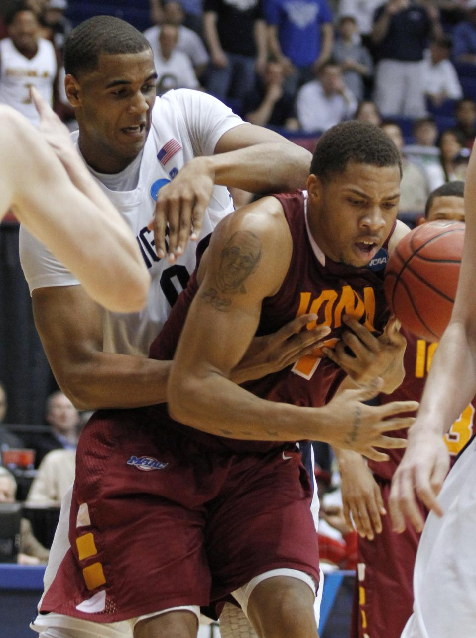 Brigham Young forward Brandon Davies, left, knocks the ball loose from Iona forward Mike Glover in the second half of an NCAA men's college basketball tournament opening-round game, Tuesday, March 13, 2012, in Dayton, Ohio. (AP Photo/Skip Peterson)