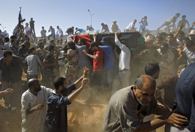 Libyan men carry the coffin, gesture and chant slogans during funeral of Libyan rebels' slain military chief Abdel-Fattah Younis in the rebel-held town of Benghazi, Libya, Friday, July 29, 2011. Thousands of mourners marched in the funeral procession Friday for the Libyan rebels' slain military chief, a day after he was gunned down under still mysterious circumstances. Abdel-Fattah Younis was killed as he traveled from his front lines operations room to the rebels' de facto capital Benghazi. (AP Photo/Sergey Ponomarev)