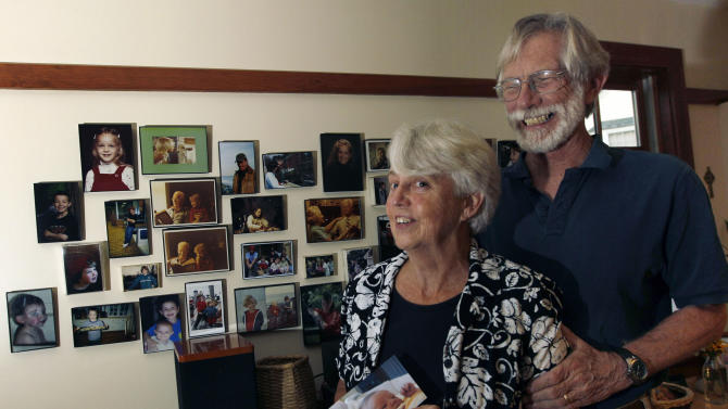 Eileen and Doug Flockhart laugh as she holds a picture of their seventh grandchild near a wall full of family photos in their home in Exeter, N.H., Wednesday, Aug. 24, 2011. America is swiftly becoming a granny state. Less frail and more engaged, today's grandparents are shunning retirement homes and stepping in more than ever to raise grandchildren while young adults struggle in the poor economy. Now making up 1 in 4 adults, grandparents are growing in numbers at twice the rate of the overall population, staying in the work force and sticking close to families, according to new census figures. (AP Photo/Elise Amendola)