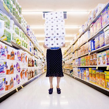 Woman-carrying-stack-of-toilet-paper-in-supermarket_web