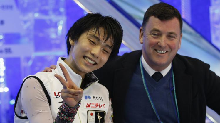 Hanyu of Japan poses with his coach Brian Orser after winning the men's free programme at the ISU Grand Prix of Figure Skating Final in Fukuoka
