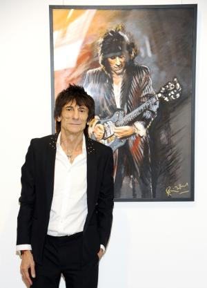 """Rolling Stones guitarist Ronnie Wood stands near one of his pieces during a news conference unveiling his new art exhibit """"Faces, Time and Places"""" on Monday, April 9, 2012, in New York. (AP Photo/Evan Agostini)"""