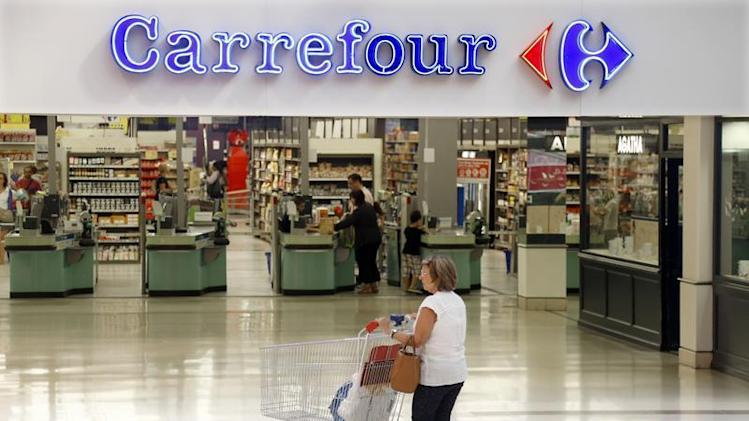 A customer pushes a shopping trolley as she arrives at the Carrefour's Bercy hypermarket in Charenton Le Pont, near Paris