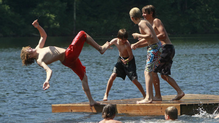 Youngsters frolic on a raft in Curtis Pond to cool off on Tuesday, July 16, 2013 in Calais, Vt. A heat wave will scorch the Northeast this week, as some of the hottest weather of the summer envelops the region. (AP Photo/Toby Talbot)