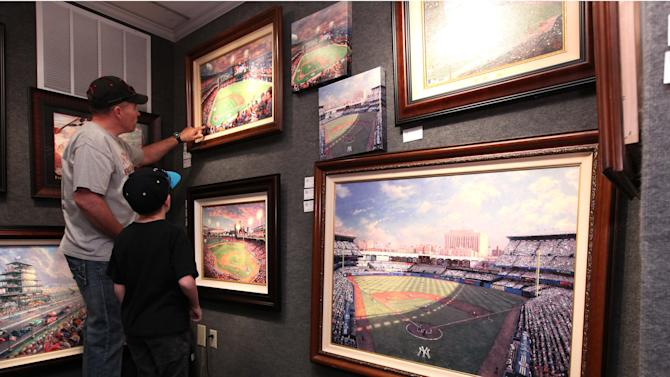 "FILE - In this April 9, 2012 file photo, Jeff Nilluka, left, and his son Jamis, 8, view the works of artist Thomas Kinkade, at Kinkade gallery in Placerville, Calif. Kinkade, 54, the self-described ""Painter of Light,"" died April 6 at his home in Los Gatos, Calif. (AP Photo/Rich Pedroncelli, file)"
