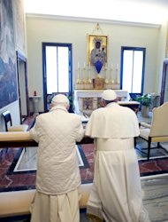 "In this photo provided by the Vatican paper L'Osservatore Romano, Pope Francis, right, and Pope emeritus Benedict XVI pray together in Castel Gandolfo Saturday, March 23, 2013. Pope Francis has traveled to Castel Gandolfo to have lunch with his predecessor Benedict XVI in a historic and potentially problematic melding of the papacies that has never before confronted the Catholic Church. The Vatican said the two popes embraced on the helipad. In the chapel where they prayed together, Benedict offered Francis the traditional kneeler used by the pope. Francis refused to take it alone, saying ""We're brothers,"" and the two prayed together on the same one. (AP Photo/Osservatore Romano, HO)"
