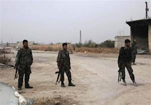 Forces loyal to Syria's President Bashar al-Assad carry their weapons as they stand along a road in the town of Tel Arn in Aleppo after capturing it from rebels