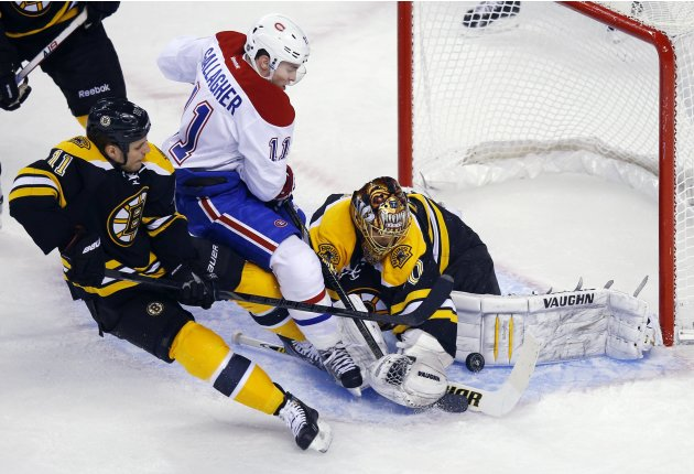Boston Bruins goaltender Tuukka Rask makes a save as Bruins center Gregory Campbell and Montreal Canadiens right wing Brendan Gallagher crash in Boston