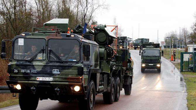 Trucks  leave the German military barracks in Vietow , eastern Germany  on their way to Luebeck-Travemuende harbour, Sunday Jan. 6, 2013. Patriot missile batteries were being prepared for shipment from Germany to Turkey on Sunday as part of efforts meant to protect the NATO (North Atlantic Treaty Organisation) ally from potential Syrian warheads. The US, Germany and the Netherlands are each deploying two batteries of the US-built defence system to boost Turkey's air defences against any spillover from Syria's nearly two-year civil war.  (AP Photo/dapd/Jens Koehler)