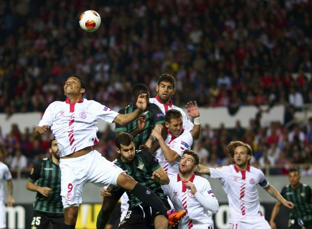 Sevilla's Carlos Arturo Bacca jumps to head the ball next to teammates and Real Betis players during their Europa League soccer match in Seville