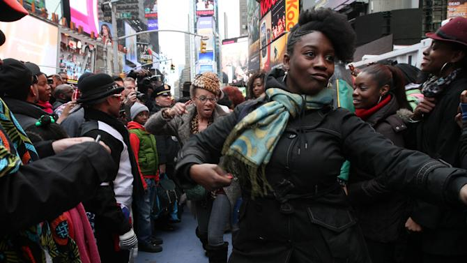 "Participants of a ""Soul Train"" line flash mob make their way along the line during a tribute to ""Soul Train"" creator Don Cornelius Saturday Feb. 4, 2012 in New York's Times Square. (AP Photo/Tina Fineberg)"