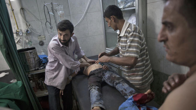 Workers at Dar El Shifa hospital try to resuscitate a Syrian boy who was killed, allegedly by Syrian Army shelling,   in Aleppo, Syria, Wednesday, Oct. 3, 2012. Three suicide bombers detonated cars packed with explosives in a government-controlled area of the battleground Syrian city of Aleppo on Wednesday, killing at least 34 people, leveling buildings and trapping survivors under the rubble, state TV said. More than 120 people were injured, the government said. (AP Photo / Manu Brabo)