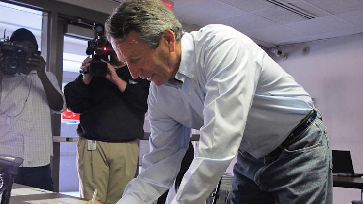 Former South Carolina Gov. Mark Sanford signs in before voting in Charleston, S.C., on Tuesday, April 2, 2013. Sanford is facing former Charleston County councilman Curtis Bostic in the Republican runoff for South Carolina's vacant 1st District congressional seat.  (AP Photo/Bruce Smith)