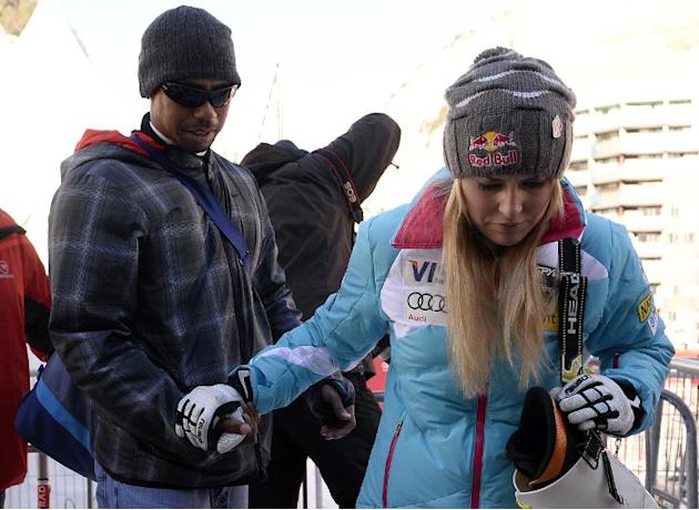 Lindsey Vonn of the US leaves with US golfer Tiger Woods after competing in the women's downhill race at the FIS Alpine Skiing World Cup in Val d'Isere in the French Alps on December 21, 2013