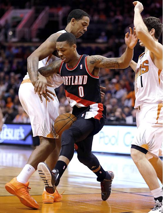 Portland Trail Blazers' Damian Lillard (0) loses the ball as Phoenix Suns' Channing Frye, left, and Goran Dragic, of Slovenia, right, defend during the first half of an NBA basketball game, Wednesday,