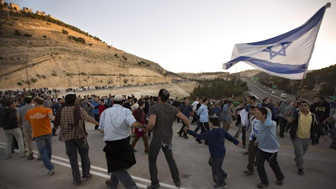 Israelis wave flags and dance as they march from the West Bank settlement of Maaleh Adumim to the E-1 area on the eastern outskirts of Jerusalem, Thursday, Feb. 13, 2014. Israel planned construction in the area E-1, or East 1, but froze under the international pressure in 2009. The construction in the area would effectively separate Palestinians in east Jerusalem from the West Bank. (AP Photo/Sebastian Scheiner)
