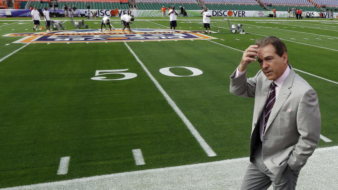 Alabama head coach Nick Saban makes his way to a microphone as workers paint the field at Sun Life Stadium during Media Day for the BCS National Championship college football game Saturday, Jan. 5, 2013, in Miami. Alabama faces Notre Dame in Monday's championship game. (AP Photo/David J. Phillip)