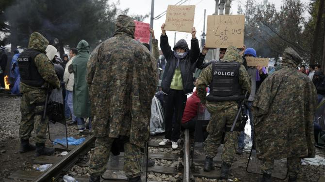 Migrants protest in front of police at the border with Greece, near Gevgelija