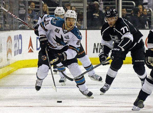 San Jose Sharks left wing T.J. Galiardi (21) and Los Angeles Kings center Jeff Carter (77) move the puck in the first period of an NHL hockey game in Los Angeles Saturday, April 27, 2013. AP Photo/Reed Saxon)